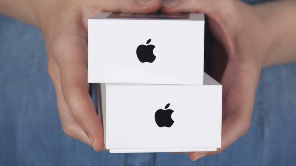 A man holding iPhone 12 boxes in his hands of the new Apple mobile phone.