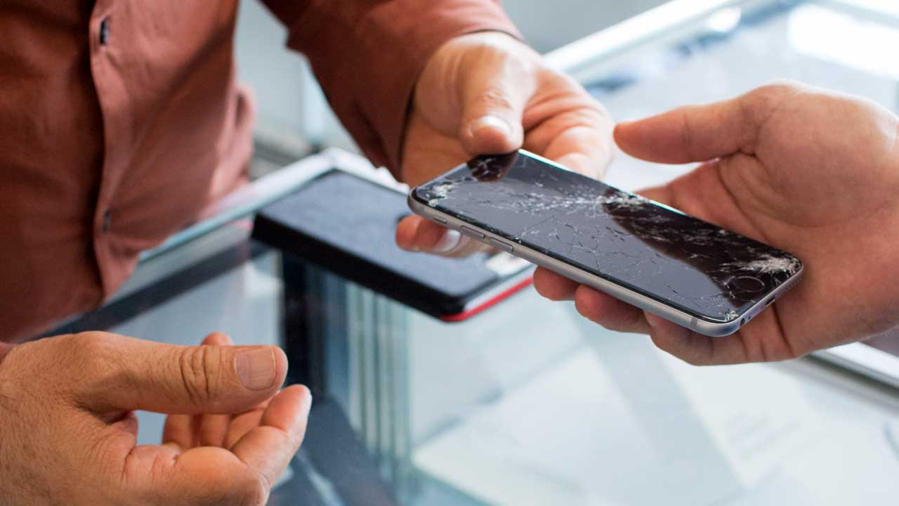Our mobile phone repair Ipswich shop takes a broken handset from a customer for a screen replacement.