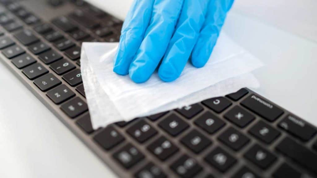 A computer keyboard being cleaned with an anti bacterial wipe cloth.